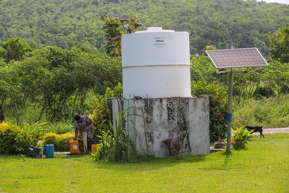 A woman on the island of Efate fills up a water container with the help of a solar pump.   Photo credit: GGGI
