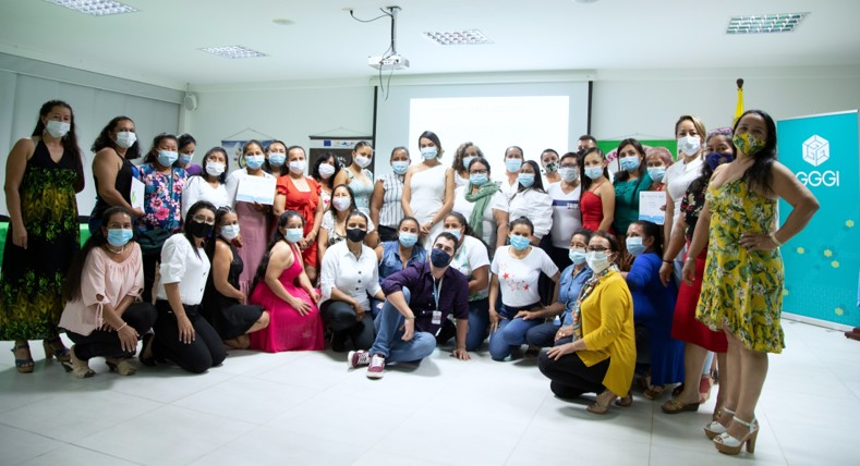 Group of 33 women wearing face masks holding diplomas and posing for the camera